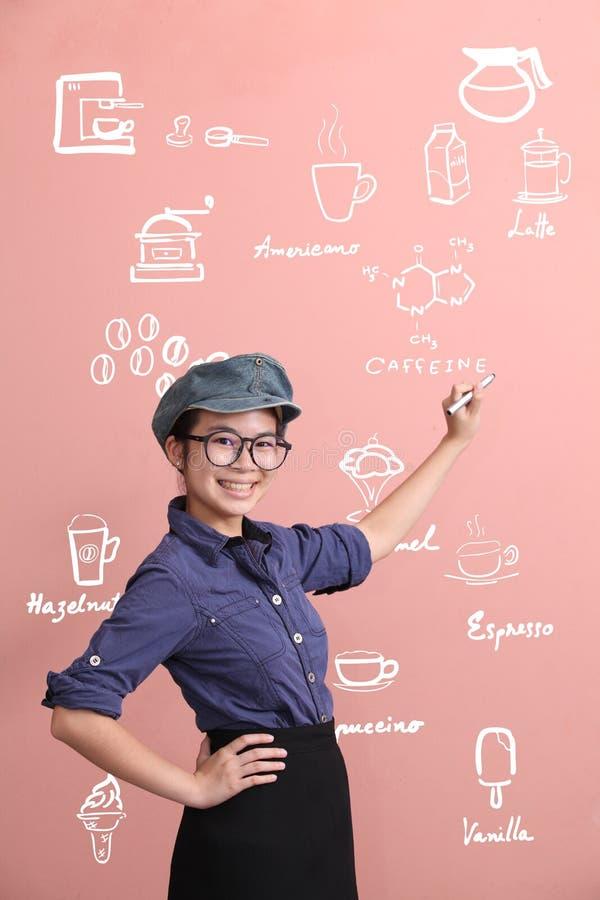 Beautiful Asian girl writing coffee menu on wall royalty free stock photography