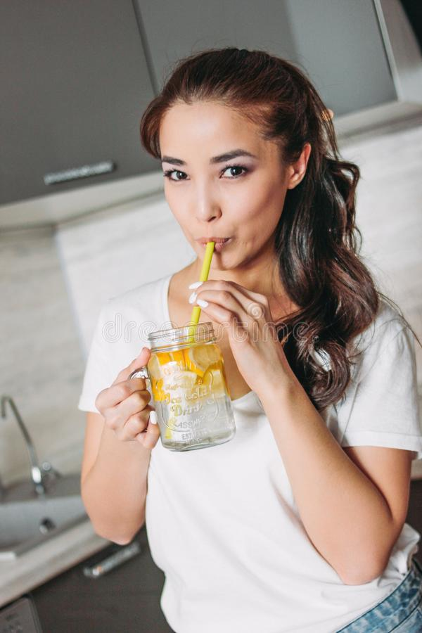 The beautiful asian girl young woman drinking glass jar with lemon water in kitchen, close up stock photo