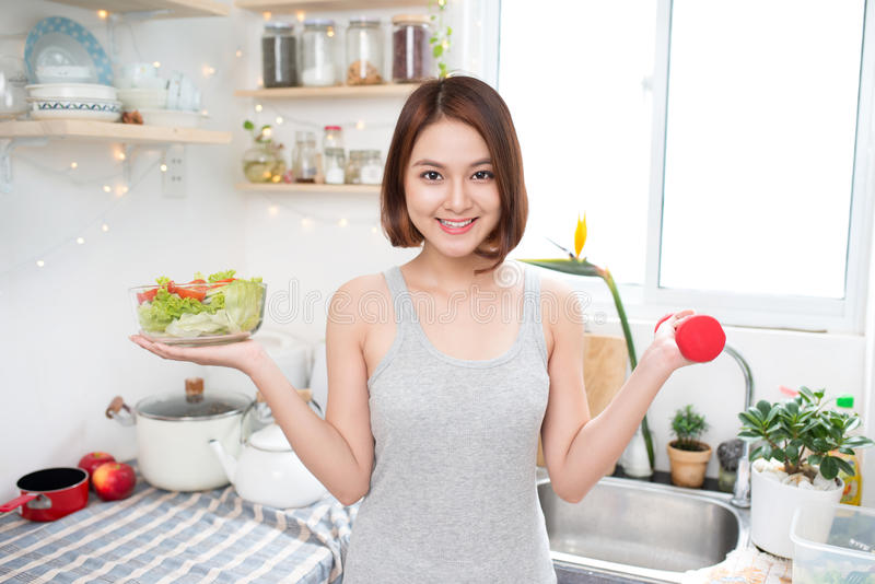 Beautiful Asian healthy girl with dumbbell and salad stock image