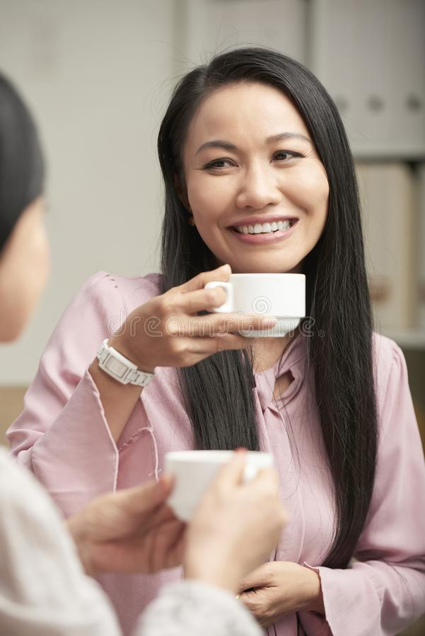Happy ethnic women having tea royalty free stock photos