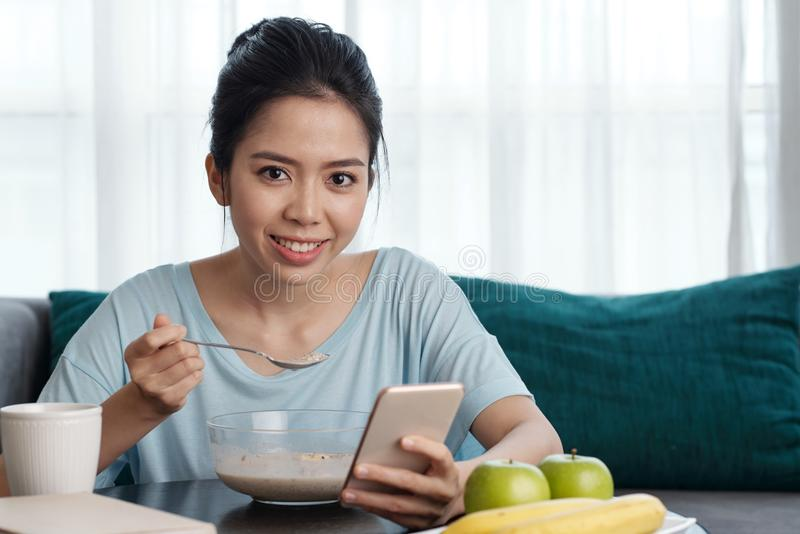 Asian woman with smartphone having breakfast royalty free stock photos
