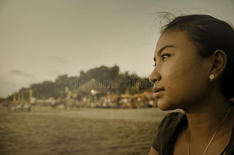 Beautiful Asian lonely woman looking to infinity lost in her thoughts sad and thoughtful sitting on sand beach. Portrait of young beautiful Asian lonely woman stock photography