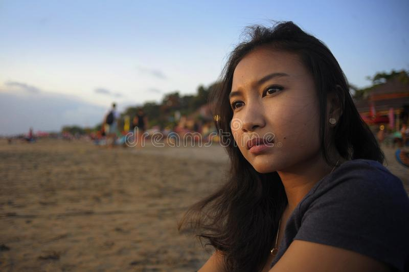 Beautiful Asian lonely woman looking to infinity lost in her thoughts sad and thoughtful sitting on sand beach. Portrait of young beautiful Asian lonely woman stock photo