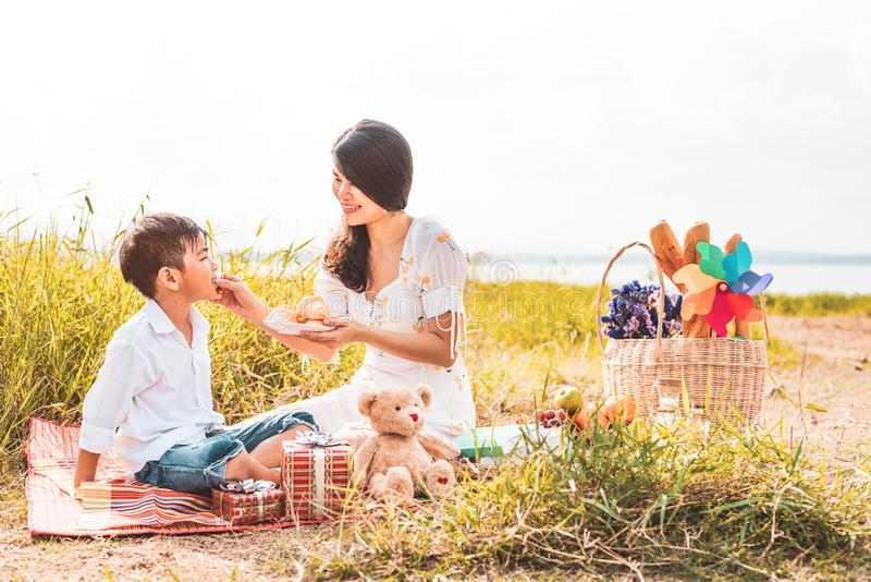 Beautiful Asian mom feeding snack to her son in meadow when doing picnic. Mother and son playing together. Celebrating in Mother stock images