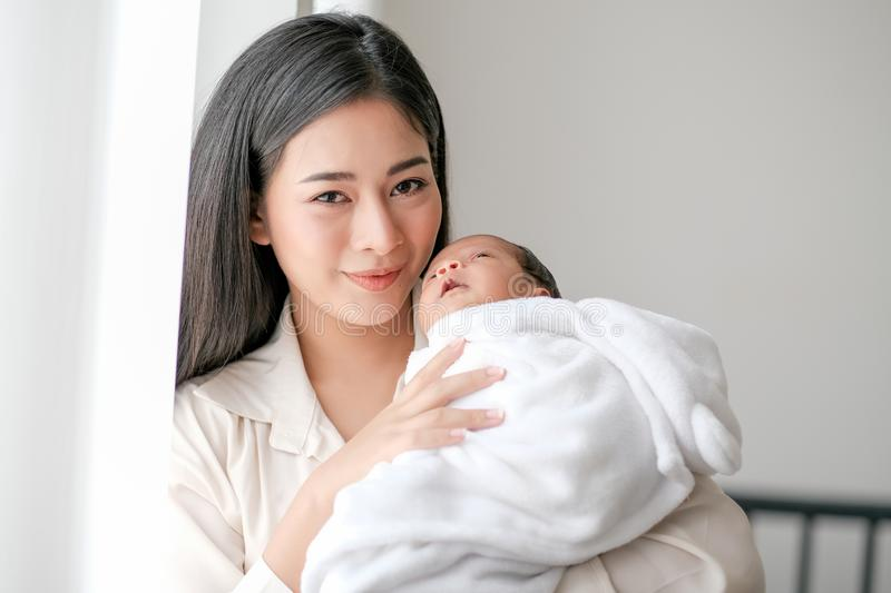 Beautiful Asian mother hold her newborn baby touch her face, smile and look forward in front of glass window with day light stock image