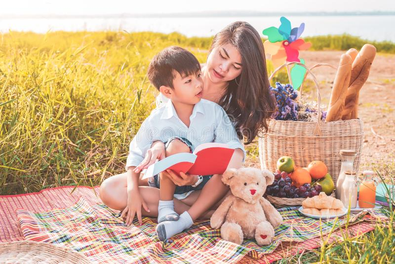 Beautiful Asian mother and son doing picnic and reading tale in red books in Easter summer party on meadow near lake and mountain stock photo