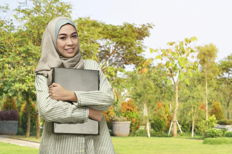 Beautiful asian muslim woman with smiley face holding laptop. In the park royalty free stock photo