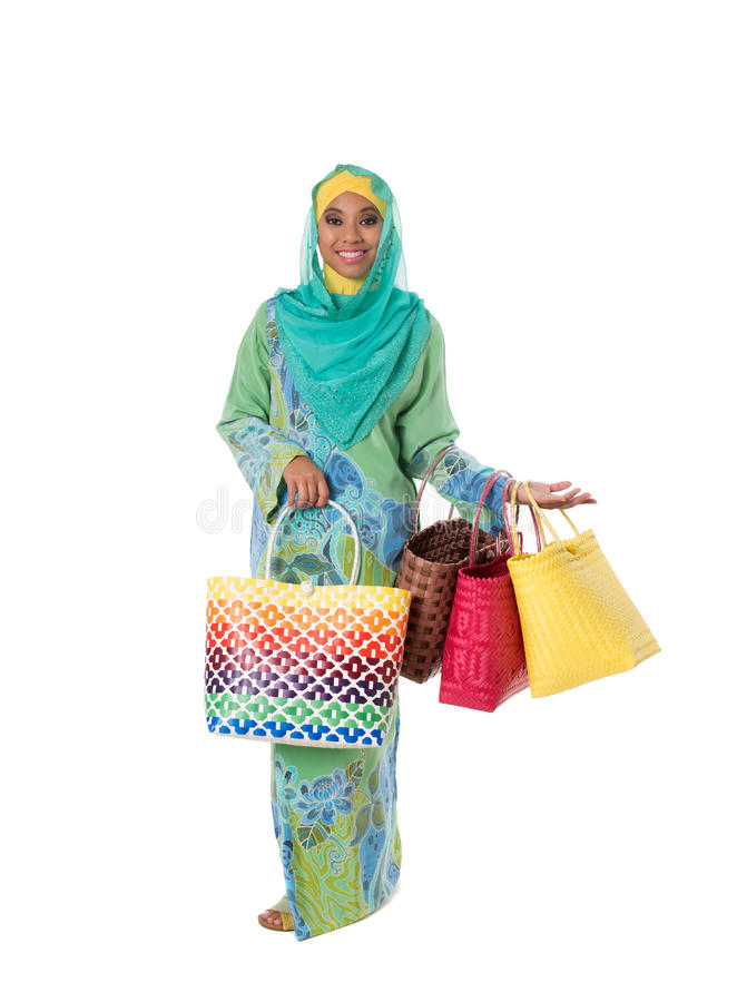 Beautiful asian muslimah woman with bright wicker tote bags.Isolated stock photo