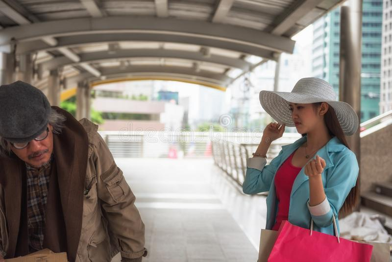 RIch woman look down to homeless man. Beautiful Asian rich women with many shopping bag look down and mean to beggar or homeless old men in urban city. bad habit stock photography