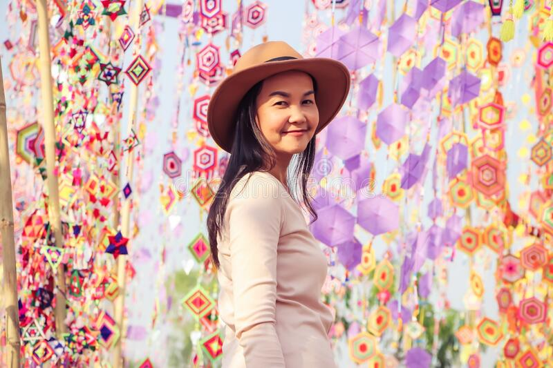 Asian tourist woman wearing hat , standing  among colorful tung flag traditiona north-eastern Thai craft smiling and looking at. Beautiful Asian tourist woman royalty free stock photography