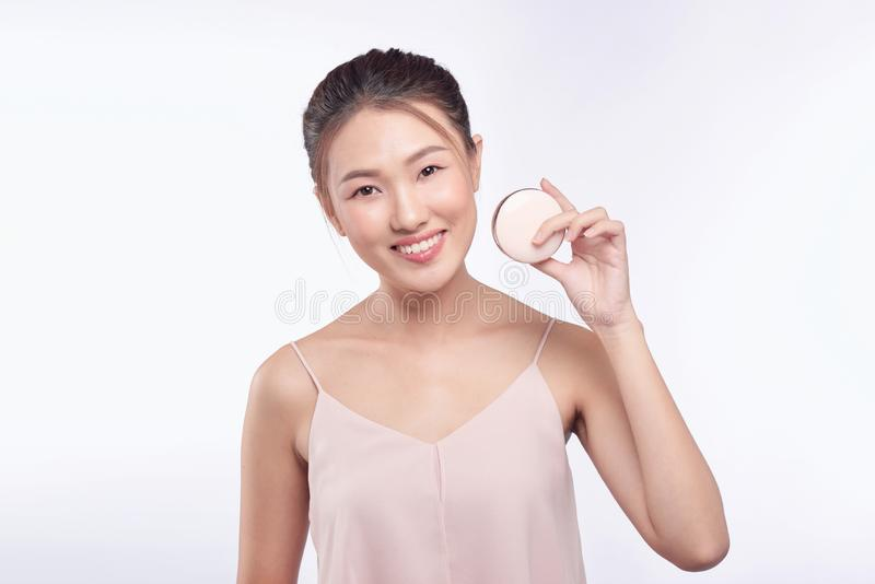 Beautiful asian woman applying powder puff at cheek makeup of cosmetic, beauty of girl with face smile.  stock image