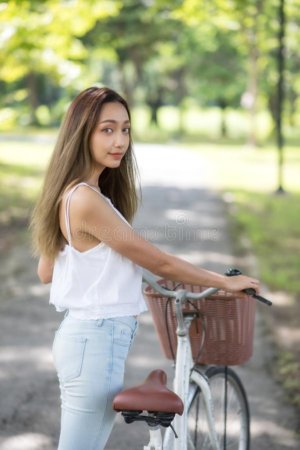 Beautiful Asian woman with bike in park stock photo