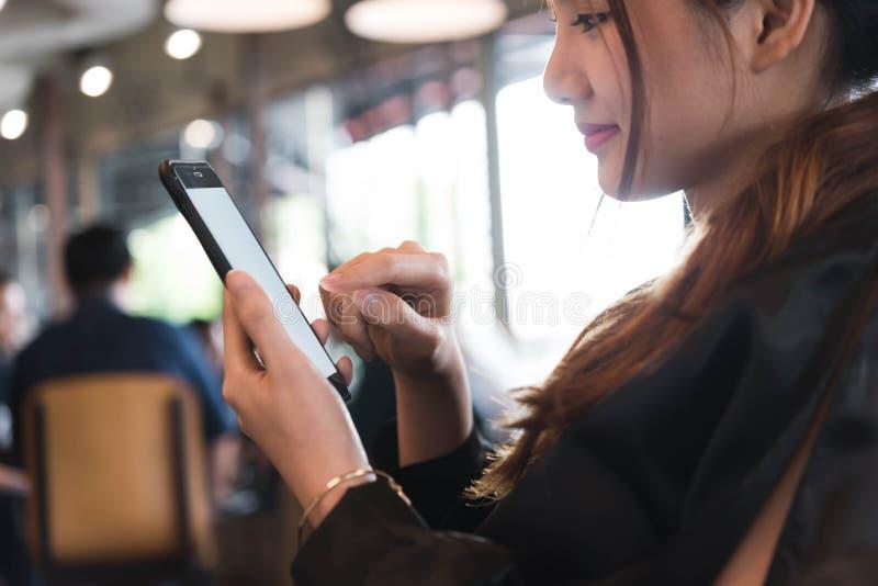Beautiful asian woman in black dress working with smartphone in. Coffeeshop stock image