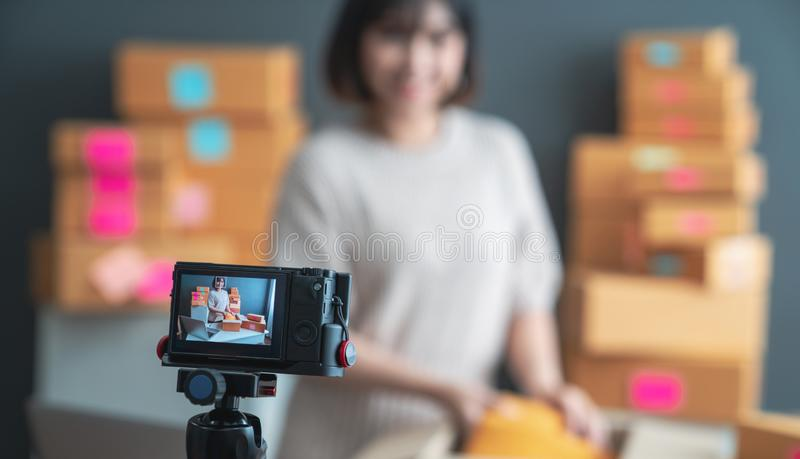 Beautiful asian woman blogger showing clothes in front of camera to recording vlog video live streaming at her shop. Business onli stock photos