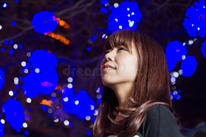 Beautiful Asian woman with blue lights in background royalty free stock image