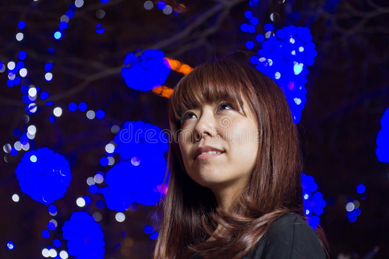 Beautiful Asian woman with blue lights in background royalty free stock photography