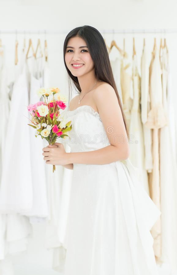 Beautiful asian woman bride in white wedding dress holding flower and smiling stock photo