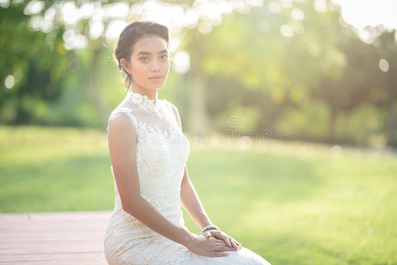 Beautiful asian woman bride in white wedding dress sit on wooden floor with green grass and tree in background royalty free stock photo