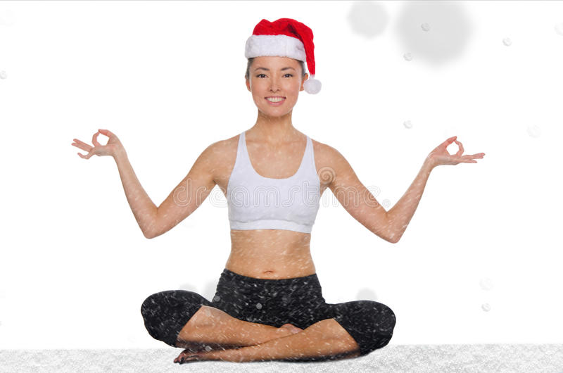 Beautiful asian woman in christmas hat with snow practicing yoga. Isolated on white stock images
