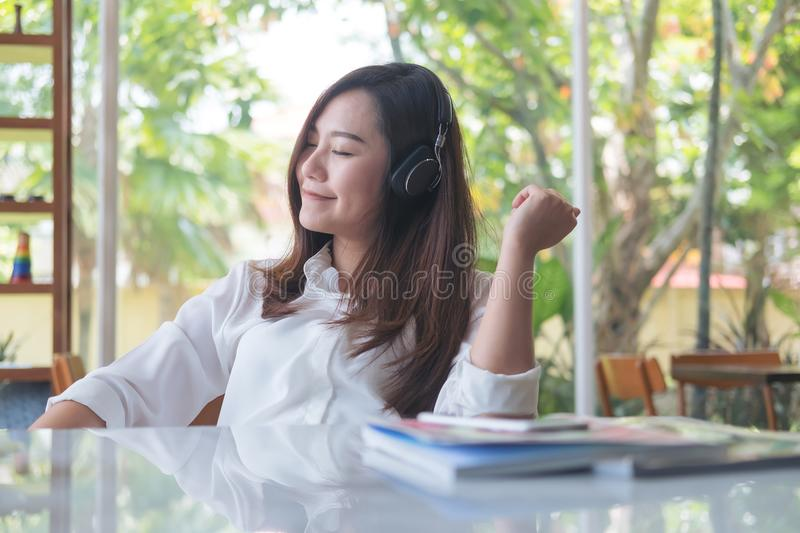 A beautiful asian woman close her eyes and enjoy listening to music with headphone in cafe with feeling relax royalty free stock photos