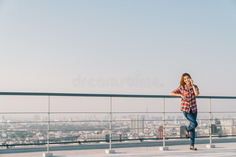 Beautiful Asian woman or college student using mobile phone call at rooftop alone or lonely, downtown cityscape background royalty free stock photo
