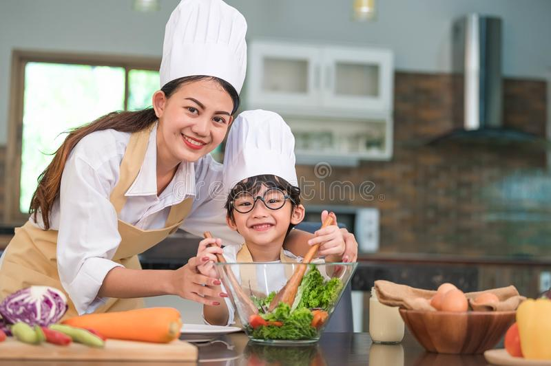 Beautiful Asian woman and cute little boy with eyeglasses prepare to cooking in kitchen at home. People lifestyles and Family. royalty free stock photos