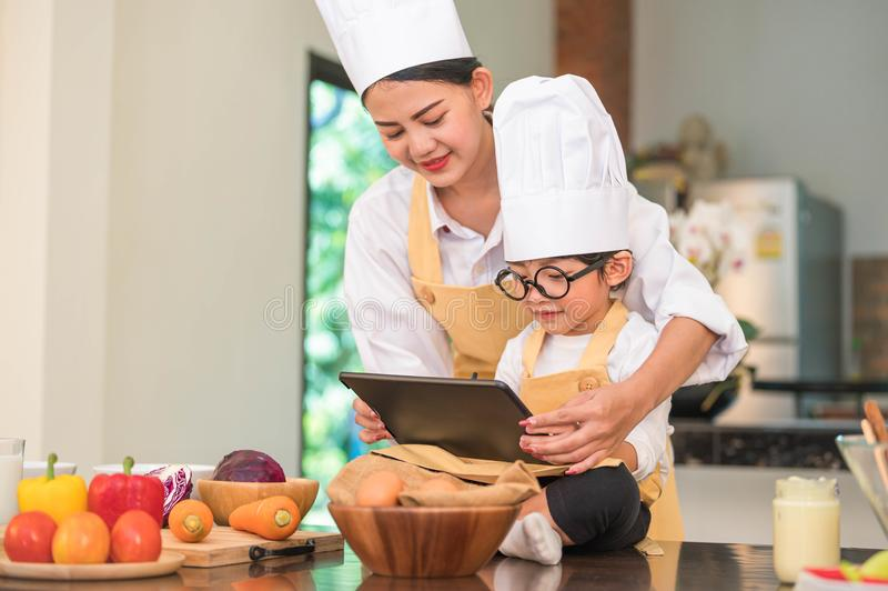 Beautiful Asian woman and cute little boy with eyeglasses prepare to cooking in kitchen at home with tablet. People lifestyles and royalty free stock photos