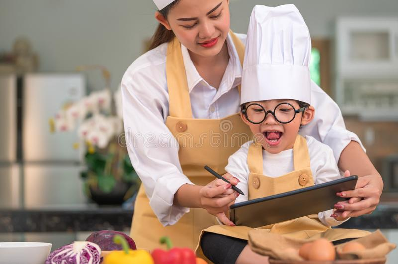Beautiful Asian woman and cute little boy prepare online shopping and listing ingredient for cooking in kitchen at home with royalty free stock photos
