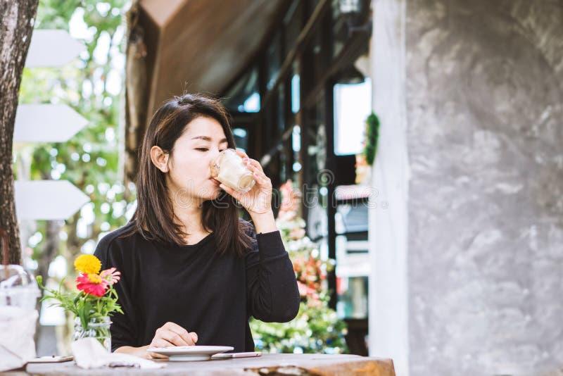 Beautiful Asian woman drinking coffee outdoors sitting at coffee shop. Young beautiful Asian woman drinking coffee outdoors sitting at coffee shop stock photo