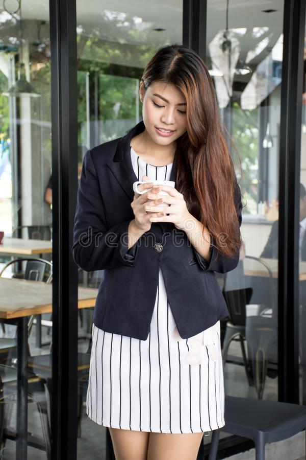 Beautiful Asian woman drinking coffee and smiling with aromatic coffee royalty free stock photography