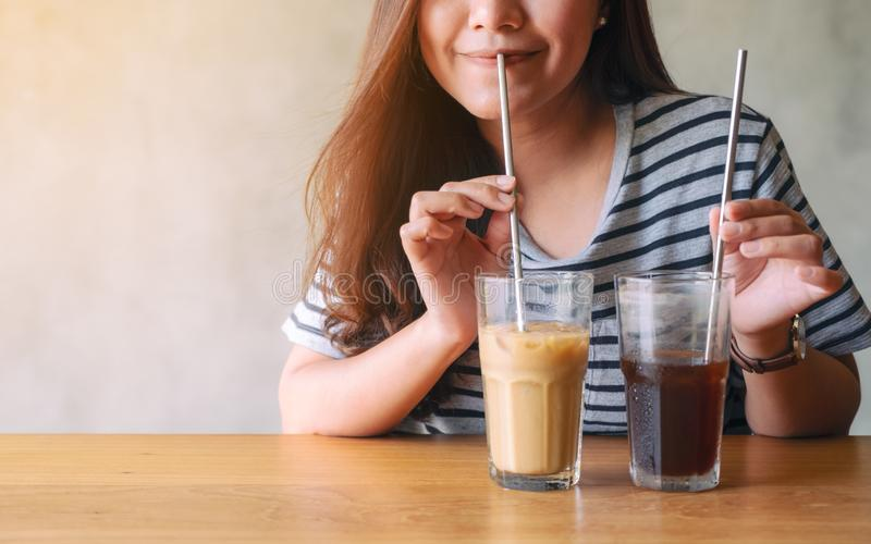 A beautiful asian woman drinking iced coffee with stainless steel straw. Closeup image of a beautiful asian woman drinking iced coffee with stainless steel straw royalty free stock images