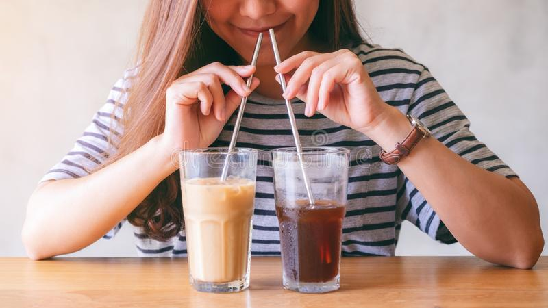 A beautiful asian woman drinking two glasses of iced coffee with stainless steel straws at the same time royalty free stock photography