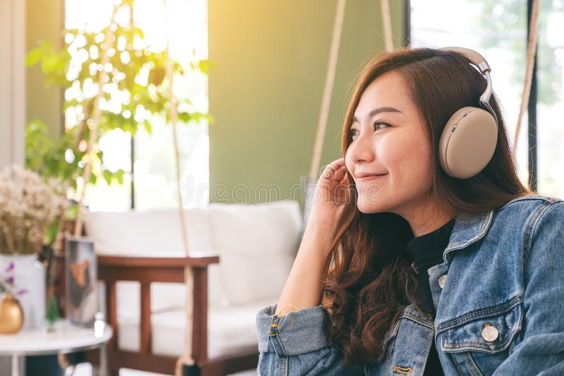 A woman enjoy listening to music with headphone with feeling happy and relaxed in cafe royalty free stock image
