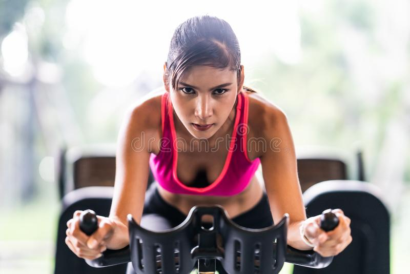 Beautiful Asian woman exercising on stationary cycling machine in indoor fitness gym, determination face. Sport training concept stock photos