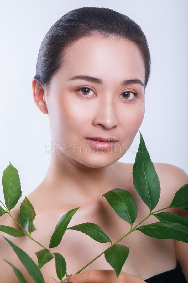 Beautiful asian woman face portrait with green leaf . Concept for skin care or organic cosmetics royalty free stock photography
