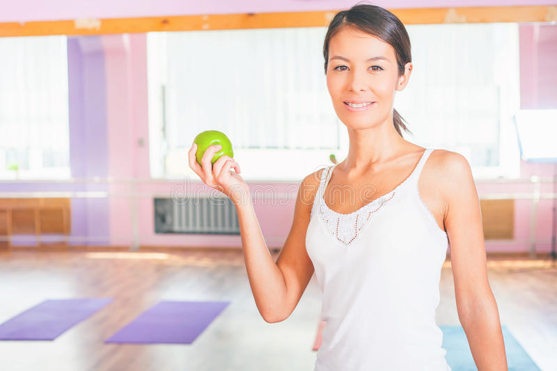 Beautiful asian woman after fitness exercise holding green apple royalty free stock photography
