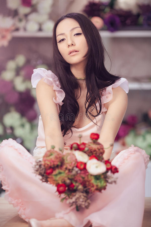 Beautiful asian woman florist in pink dress with bouquet of flowers in hands in flower store stock photo