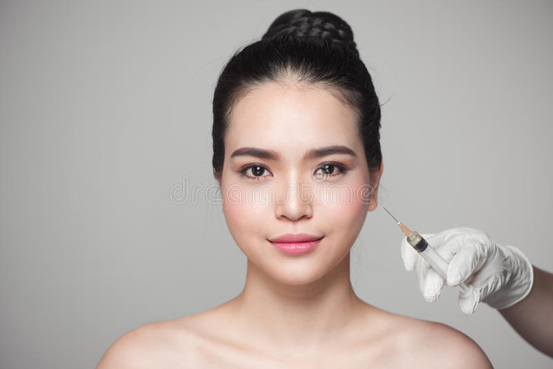 Beautiful asian woman gets beauty facial injections. Face aging royalty free stock photography