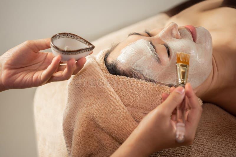 Beautiful Asian Woman getting facial nourishing at spa salon. Masseuse hands doing Face Massage. treatment, skincare, Facial Cleansing, Moisturizer stock photo