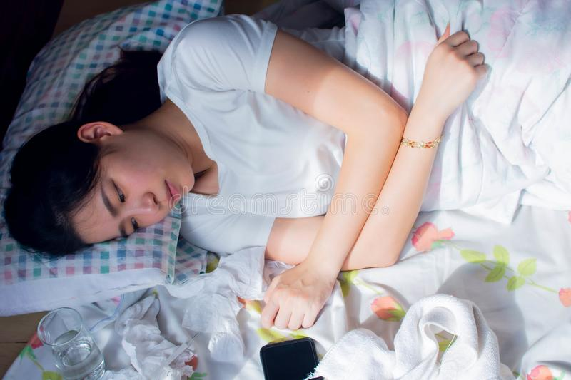 A woman getting sick and headache while laying on her bed royalty free stock images