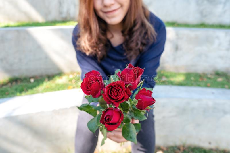 Beautiful asian woman giving red roses flower to her boyfriend on Valentine`s day with feeling happy and loved. A beautiful asian woman giving red roses flower stock photography