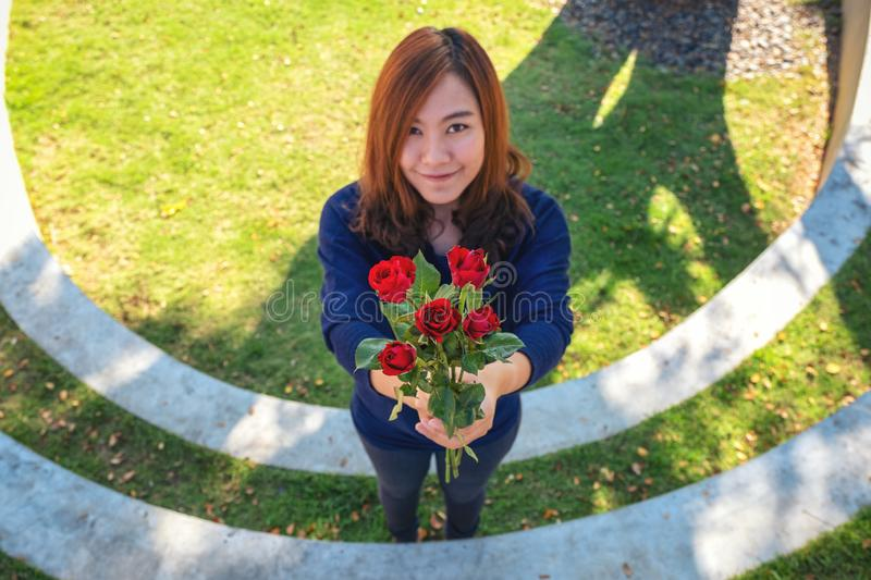 Beautiful asian woman giving red roses flower to her boyfriend on Valentine`s day with feeling happy and loved. A beautiful asian woman giving red roses flower stock photos