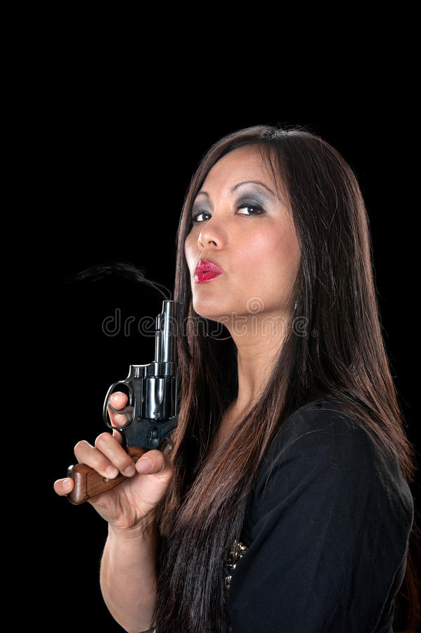 Beautiful Asian woman with gun. A beautiful, sinister Asian woman holding a pistol and blowing on the smoke coming out of the barrel royalty free stock images