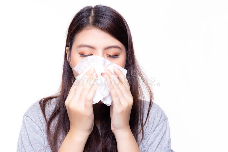 Beautiful asian woman has a cold or flu. She feel sick and dizzy. Pretty girl blowing nose by using tissue paper. She has nasal. Congestion or stuffed nose and royalty free stock photography