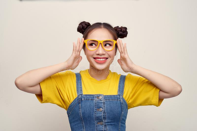 Beautiful Asian woman has two buns of hair wearing a jeans dungaree and adjusting glasses royalty free stock photos