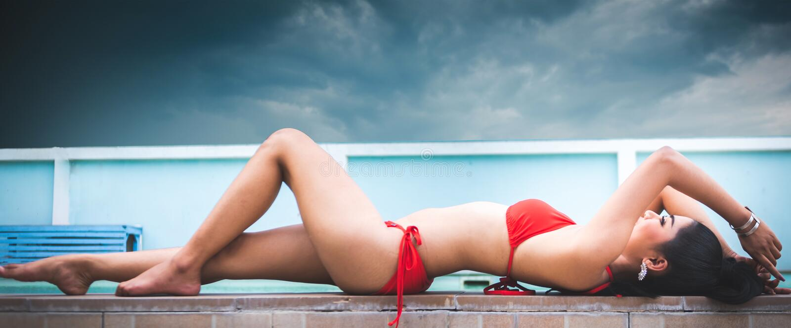 Beautiful Asian woman laying down beside swimming pool outdoor with red swimming suit royalty free stock image