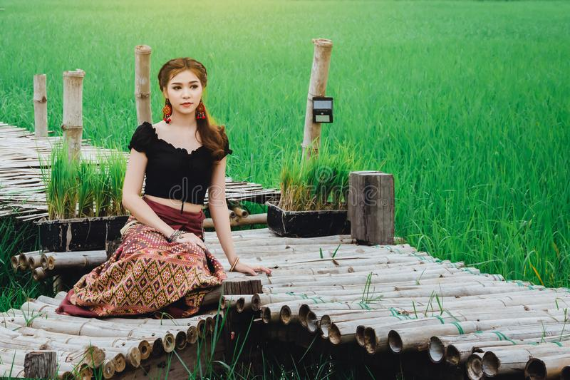 Beautiful Asian woman in local dress sitting and enjoy natural on bamboo bridge royalty free stock image