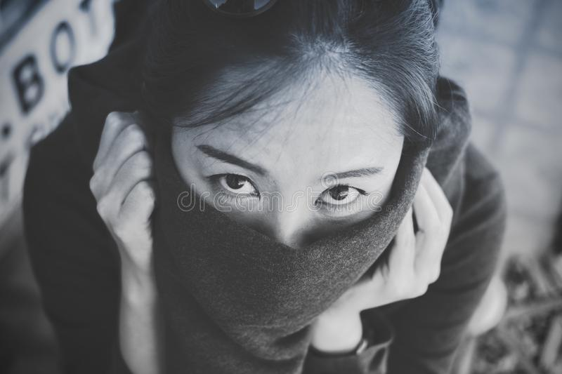A beautiful Asian woman looking and closing her mouth with cloth stock photos