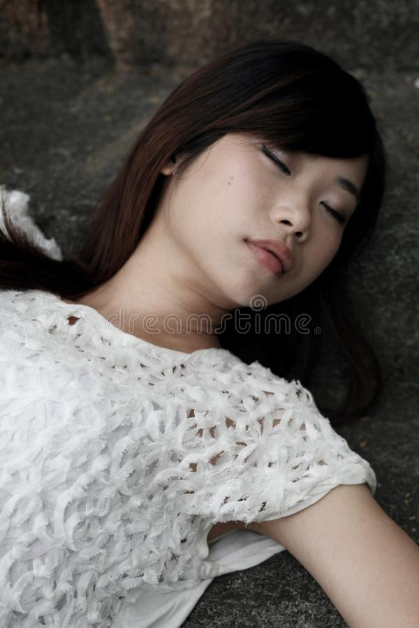 Beautiful Asian woman lying down with her eyes closed royalty free stock photos