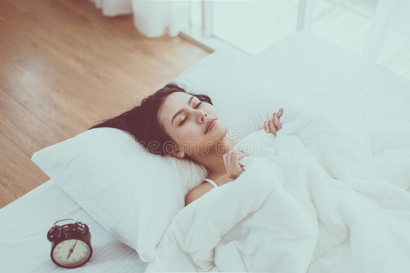 Beautiful asian woman lying under blanket and waking up in her bedroom at the morning,Happy and smiling stock photo